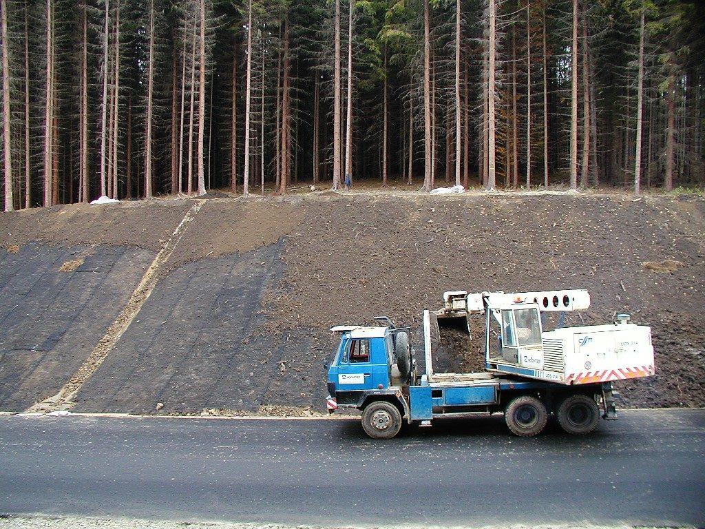 Přesypávání protierozních georohoží zeminou z nakladače UDS