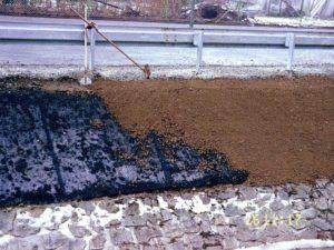 Plastová protierozní rohož částečně zasypaná zeminou